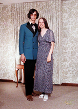 Gary and his girlfriend posing at her prom, he in a blue tuxedo with thick sideburns, 70s style long hair, and pink tinted glasses.